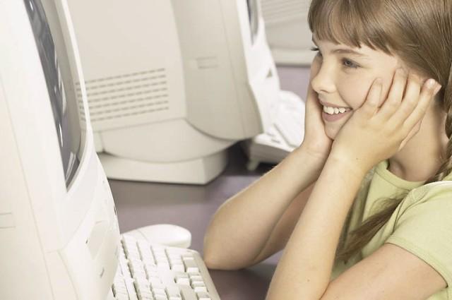 Smiling little schoolgirl using computer 1