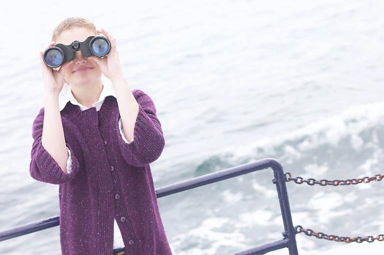 Woman looking through binoculars on boat
