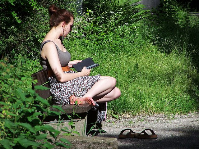 ereader, woman reading on bench, wolf g, flickr