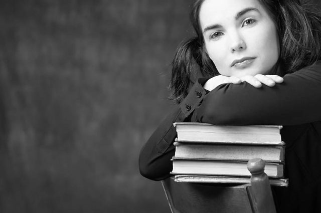 woman leaning on pile of books