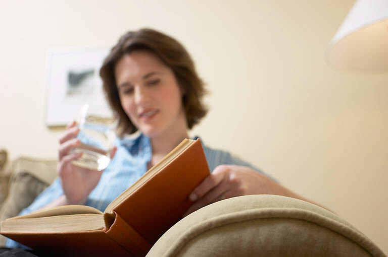 Woman reading book and drinking glass of water