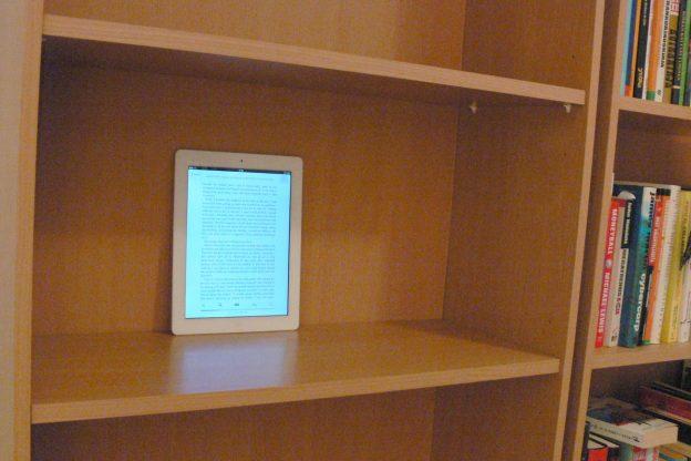 Apple iPad on bookshelf with books