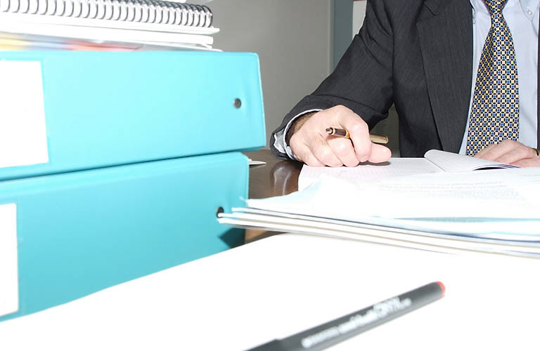 man writing at office desk, stack of folders in front