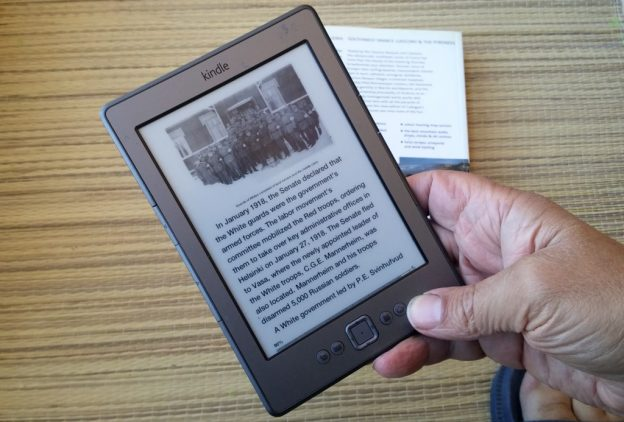 Amazon Kindle ereader in hand, books in the background