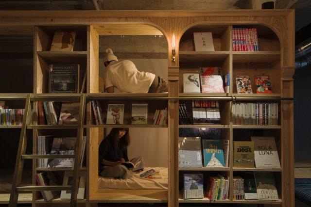 sleeping in a capsule in a bookshelf in Tokyo hostel