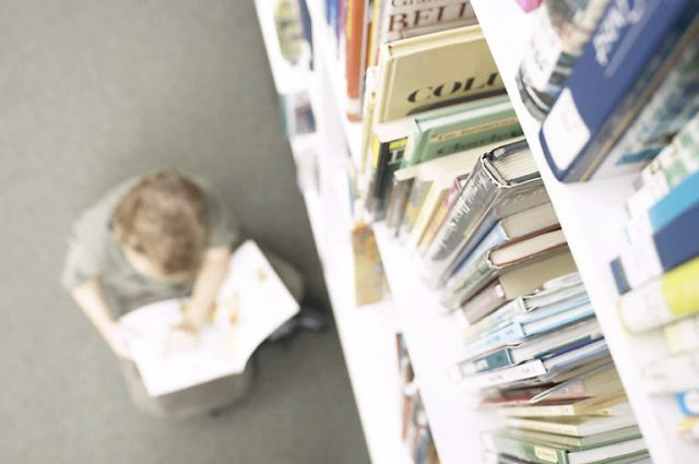 boy reading in library, books on a shelf