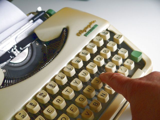 mechanical typewriter, finger pushing a key, writing, typing