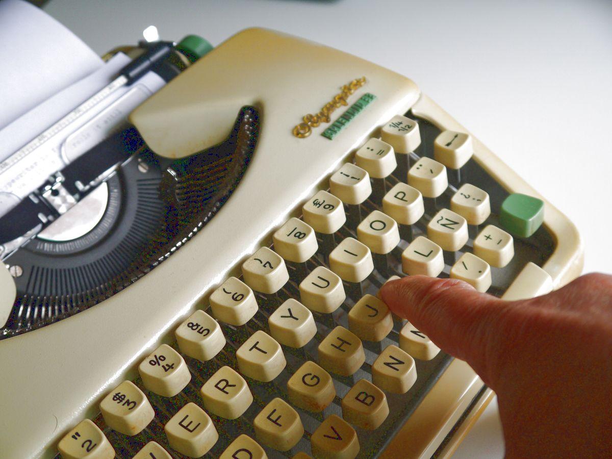 mechanical typewriter, finger pushing a key, writing, typing