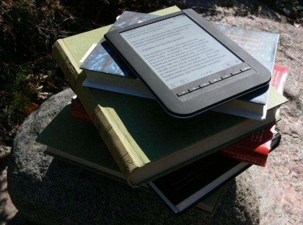 e-reader on top of paper book stack in sunshine