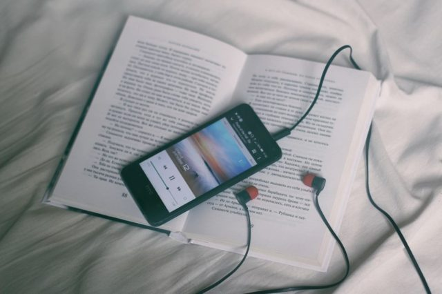 book, phone, headphones, on bed