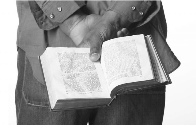 man holding an open book behind his back