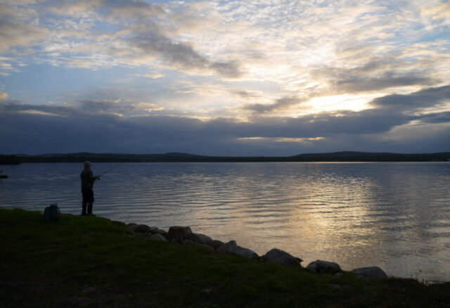 a fisherman in midnight sun at Lake Inari, Lapland