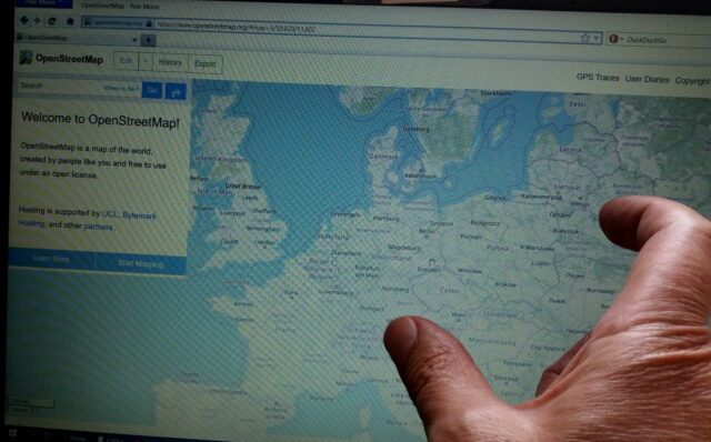 finger pointing at a map on laptop screen